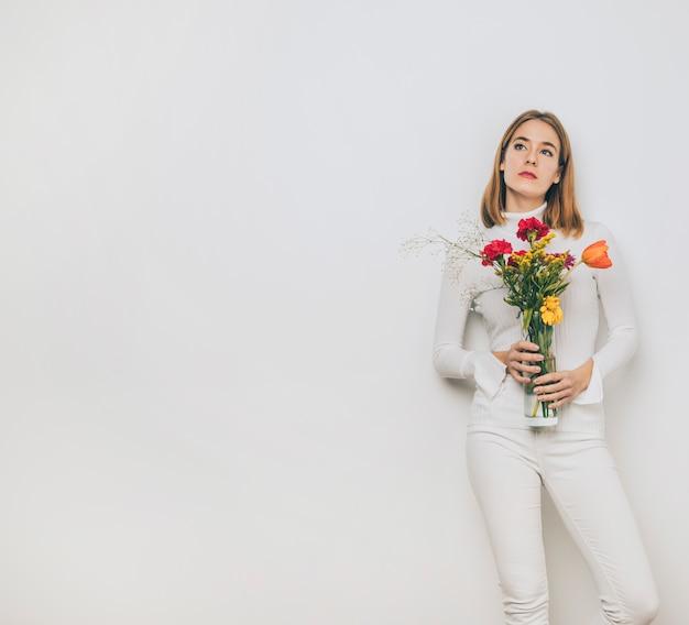 Jovem pensativa com flores em vaso