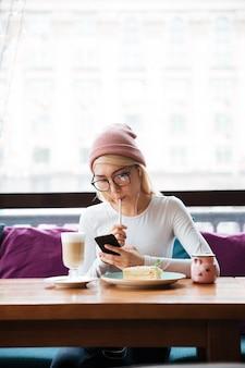 Jovem pensativa comendo e usando o smartphone no café