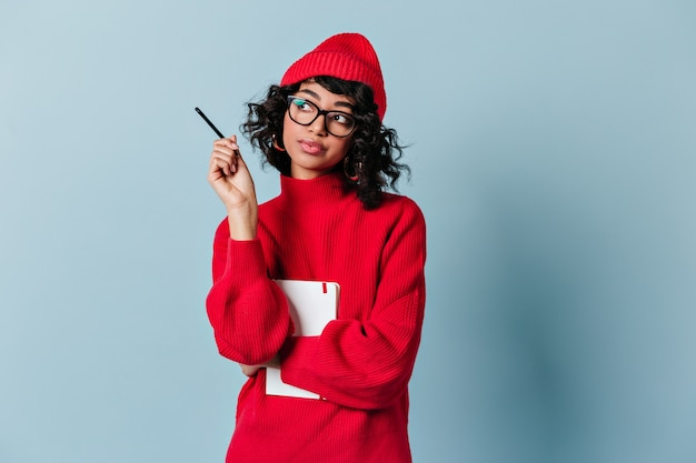 Jovem pensativa de óculos e chapéu vermelho olhando para longe