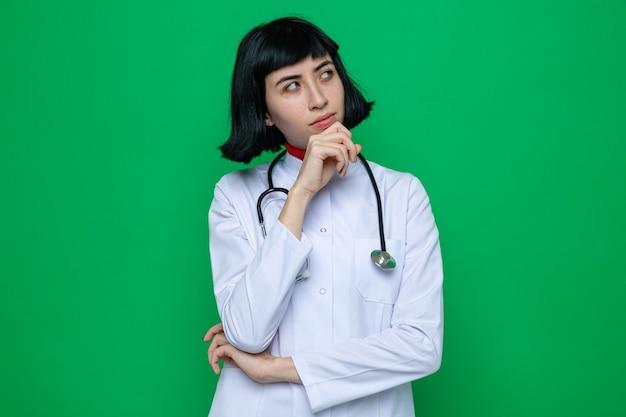 Jovem pensativa e bonita caucasiana com uniforme de médico com estetoscópio colocando a mão no queixo e olhando para o lado