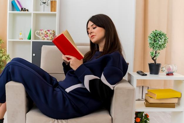 Jovem pensativa e bonita caucasiana sentada em uma poltrona em uma sala de estar projetada lendo um livro