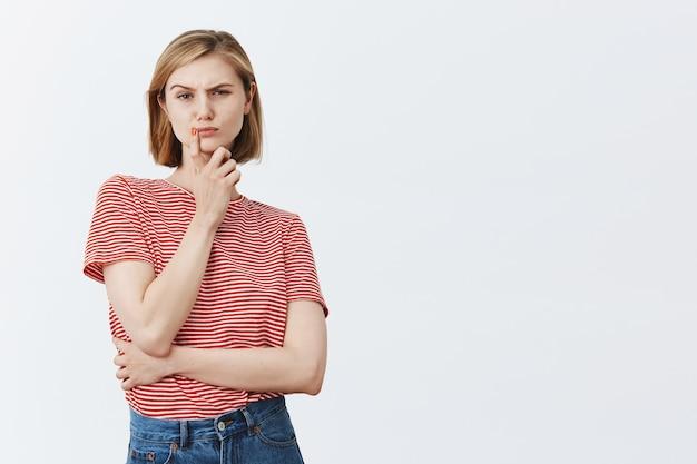 Jovem pensativa e duvidosa pensando, parecendo complexa e hesitante, ponderando sobre uma decisão