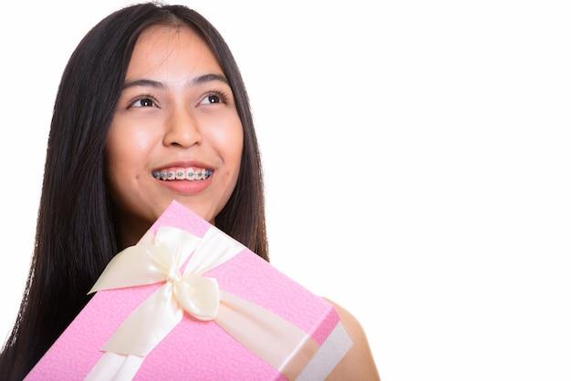 Jovem pensativa e feliz adolescente asiática sorrindo enquanto segura um presente