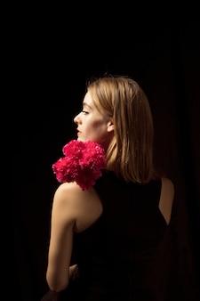 Jovem pensativa em pé com flores cor de rosa