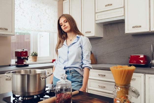 Jovem pensativa em pé na cozinha pensando no que cozinhar