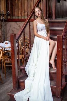 Jovem pensativa em um vestido longo branco sentada na escada