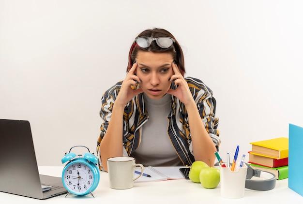 Jovem pensativa estudante de óculos na cabeça, sentada na mesa com ferramentas universitárias, colocando os dedos nas têmporas, olhando para o lado isolado na parede branca