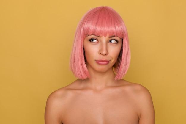 Jovem pensativa, linda mulher de olhos azuis com corte de cabelo curto rosa, mantendo os lábios dobrados enquanto olha pensativamente de lado, tramando algo enquanto posa sobre uma parede de mostarda