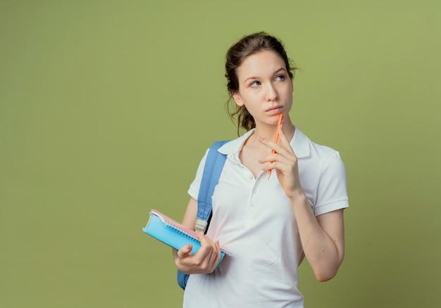Jovem pensativa, muito bonita, aluna usando uma bolsa traseira, olhando para o lado, segurando o bloco de notas e o livro e tocando o queixo com uma caneta isolada em um fundo verde oliva com espaço de cópia