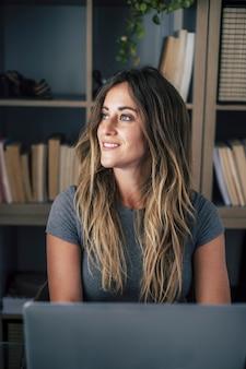 Jovem pensativa olhando para longe enquanto trabalhava no laptop. feliz empresária sonhando enquanto trabalhava em casa. mulher sorridente, sonhando acordada, sentada em casa em frente ao laptop