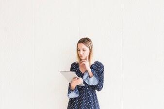 Jovem pensativa olhando tablet digital na frente da parede