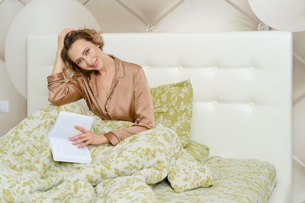 Jovem pensativa sentada na cama com um livro