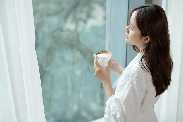 Jovem pensativa tomando café da manhã e olhando para fora pela janela do apartamento