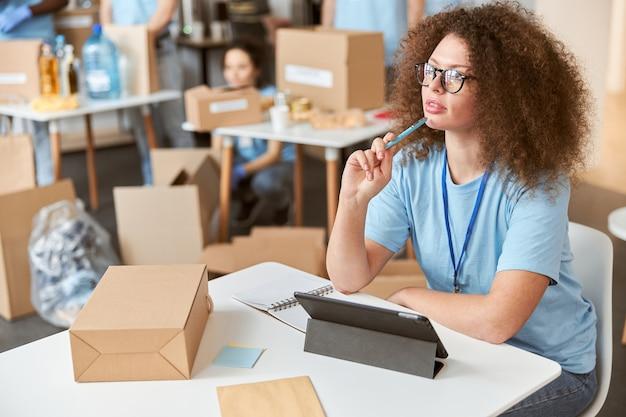 Jovem pensativa, voluntária em uniforme azul, olhando para longe usando o tablet pc enquanto está sentada