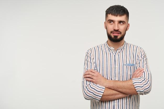 Jovem pensativo atraente, barbudo, de cabelos escuros, mantendo as mãos cruzadas enquanto olha pensativamente para o lado, vestido com uma camisa listrada enquanto posa sobre uma parede branca