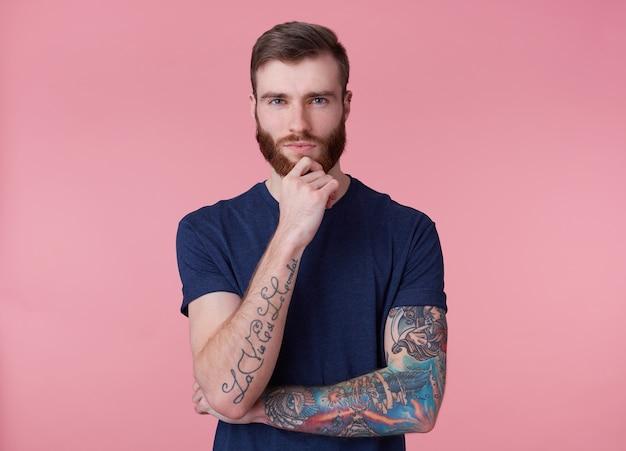 Jovem pensativo atraente cara de barba vermelha com olhos azuis, vestindo uma camiseta azul, segura a mão em seu queixo e olha pensativo para a câmera isolada sobre fundo rosa.