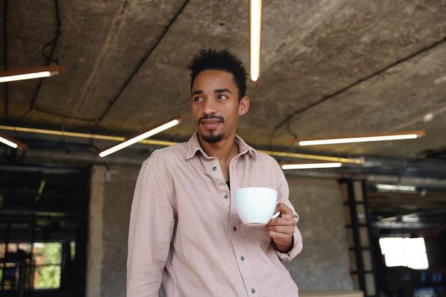 Jovem pensativo, barbudo, com pele escura, em pé em frente ao café da cidade, bebendo café enquanto espera seu pedido, olhando para o lado com uma expressão pensativa