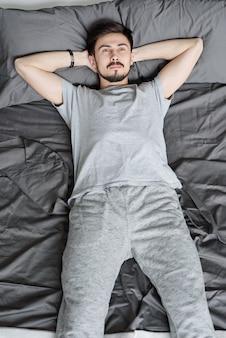 Jovem pensativo barbudo em trajes caseiros deitado com as mãos atrás da cabeça na cama enquanto relaxa na quarentena