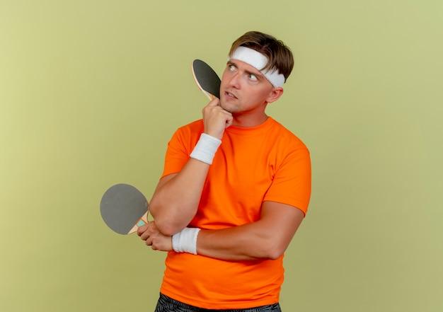 Jovem pensativo, bonito, esportivo, usando bandana e pulseiras, olhando para o lado, segurando raquetes de pingue-pongue, colocando as mãos embaixo do queixo e do cotovelo