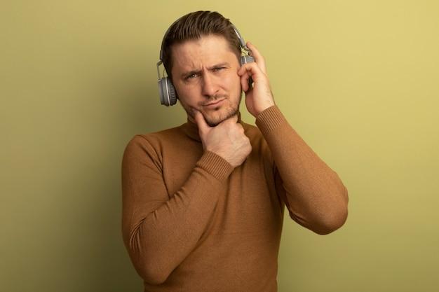 Jovem pensativo, bonito, loiro, usando e segurando fones de ouvido, tocando o queixo, olhando para a frente, isolado na parede verde oliva com espaço de cópia