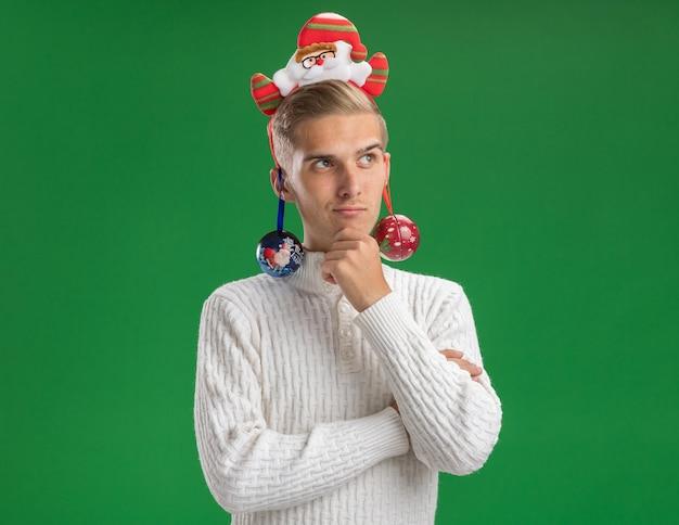 Jovem pensativo bonito usando bandana de papai noel tocando o queixo olhando para o lado com enfeites de natal pendurados em suas orelhas isoladas na parede verde