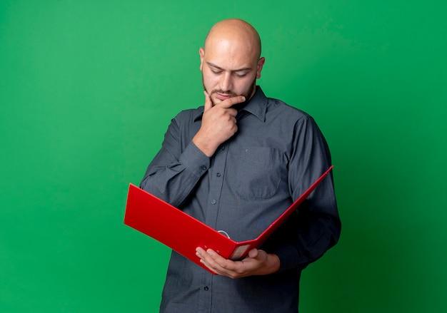 Jovem pensativo careca homem de call center segurando o queixo segurando e olhando para uma pasta aberta isolada na parede verde