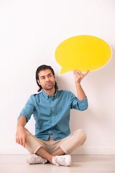 Jovem pensativo com a barba por fazer, sentado com as pernas cruzadas no chão e segurando uma etiqueta de balão perto da cabeça