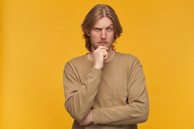 Jovem pensativo, com cabelos loiros, barba e bigode. vestindo um suéter bege. tocando seu queixo e levanta uma sobrancelha. isolado sobre a parede amarela