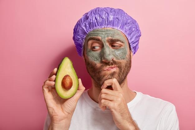 Jovem pensativo com máscara de argila no rosto, segura uma fatia de abacate, recebe tratamentos de spa, segura o queixo, tem barba por fazer, usa touca de banho, camiseta branca