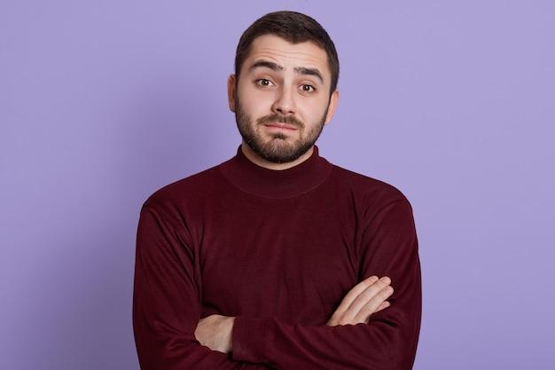 Jovem pensativo com olhar cético, duvidoso e desconfiado, posando contra um fundo lilás com as mãos postas, vestindo um suéter cor de vinho