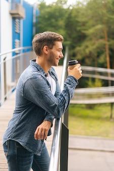 Jovem pensativo confiante em pé no terraço da varanda e bebendo café encostado no corrimão