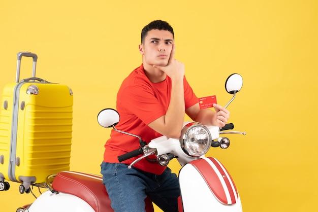 Jovem pensativo de frente para um ciclomotor segurando um cartão de desconto e colocando a mão no queixo