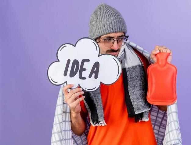 Jovem pensativo doente usando óculos, chapéu de inverno e lenço envolto em xadrez segurando uma bolha de ideia e uma bolsa de água quente, olhando para uma bolsa de água quente isolada na parede roxa com espaço de cópia