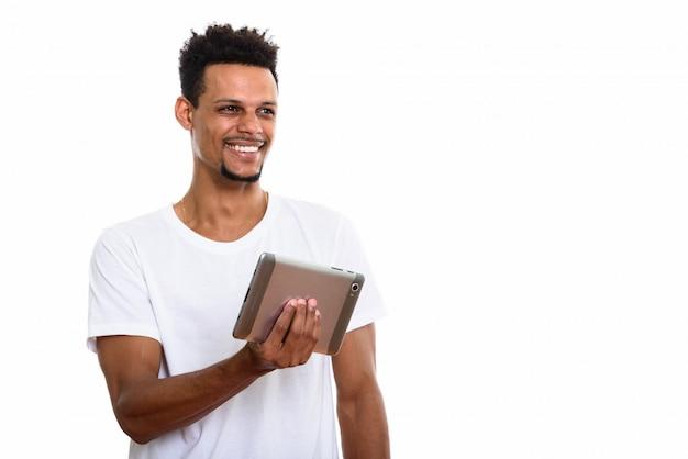 Jovem pensativo e feliz homem africano sorrindo enquanto segura um tablet digital