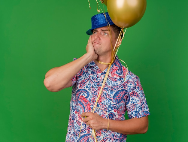 Jovem pensativo e festeiro olhando para o lado usando um chapéu azul segurando balões amarrados no pescoço colocando a mão na bochecha isolada no verde