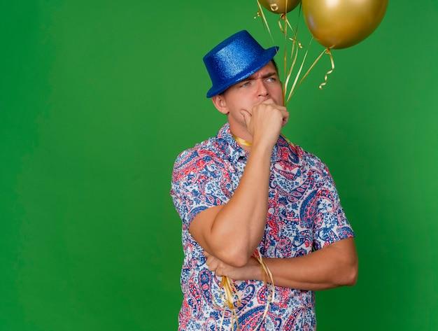 Jovem pensativo e festeiro olhando para o lado usando um chapéu azul segurando balões amarrados no pescoço e colocando a mão na boca isolada no verde