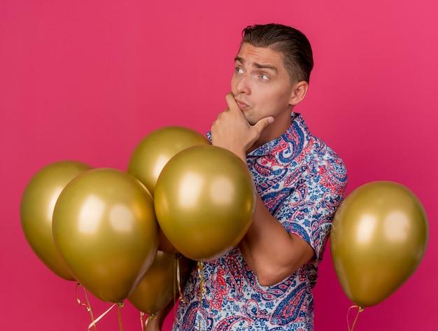 Jovem pensativo e festeiro olhando para o lado vestindo uma camisa colorida em pé entre balões e colocando a mão no queixo isolado no rosa