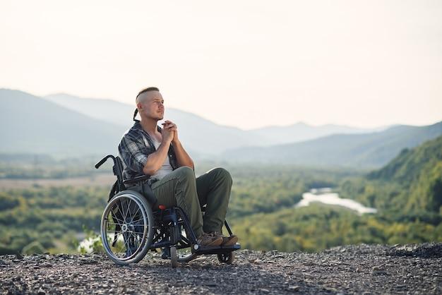 Jovem pensativo em uma cadeira de rodas apreciando a beleza da natureza nas montanhas