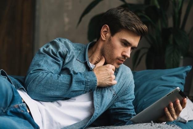 Jovem pensativo olhando para tablet digital