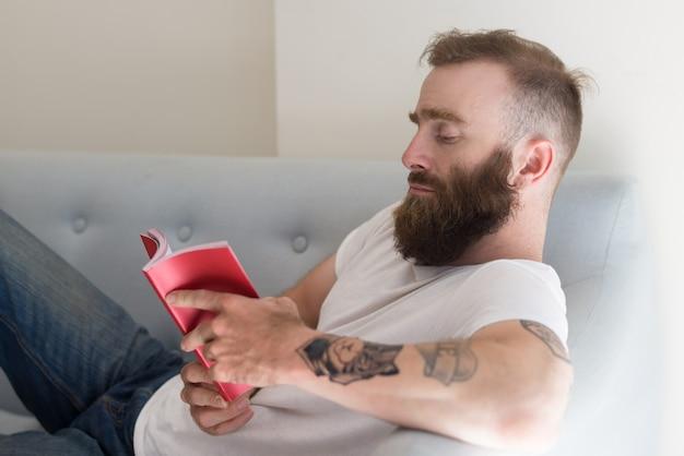 Jovem pensativo sério com tatuagem deitado no sofá