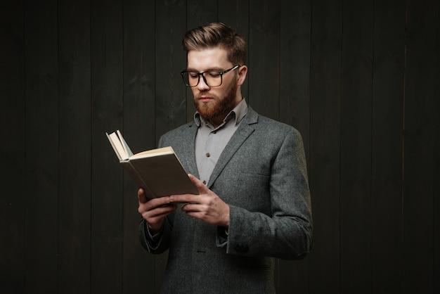 Jovem pensativo usando óculos em pé e lendo um livro isolado no fundo preto de madeira