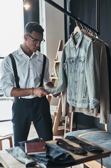 Jovem perfeccionista. jovem pensativo tocando uma jaqueta jeans enquanto estava no showroom