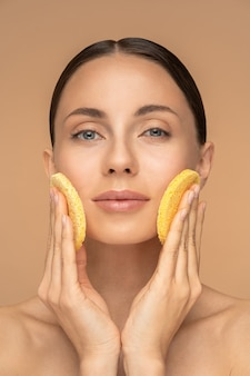 Jovem perfeita com maquiagem nude e ombros nus limpando o rosto com uma esponja esfoliante