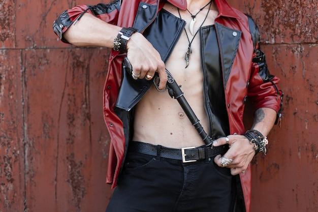 Jovem perigoso em uma jaqueta de couro elegante em jeans preto com amuletos com pulseiras com arma vintage está de pé perto de uma parede enferrujada ao ar livre. close de um corpo masculino com o torso nu.