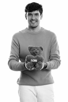 Jovem persa feliz sorrindo enquanto segura o ursinho de pelúcia com uma placa de coração e amor pronta para o dia dos namorados