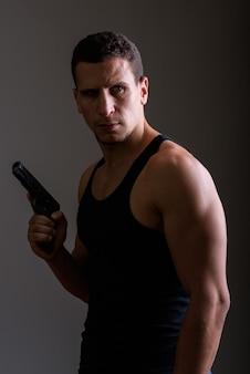 Jovem persa musculoso e pensativo segurando uma arma e olhando para trás