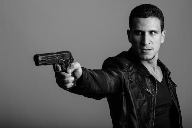 Jovem persa musculoso e zangado com o objetivo de atirar com uma arma contra uma parede cinza