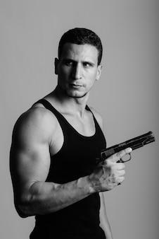 Jovem persa musculoso pensando enquanto segura a arma contra uma parede cinza
