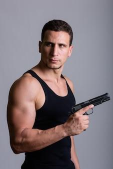 Jovem persa musculoso pensando enquanto segura uma arma