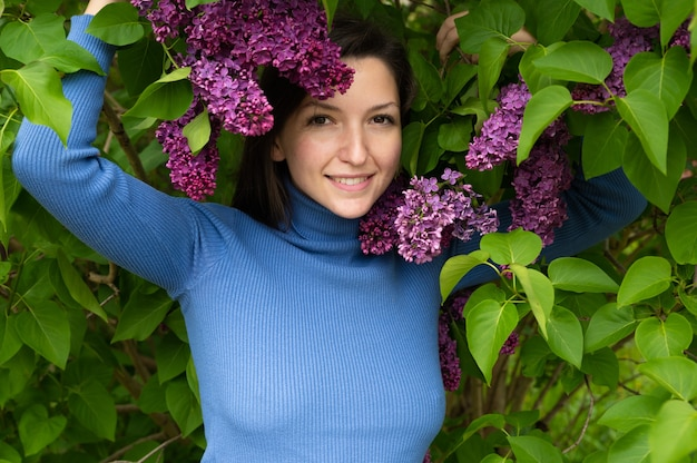 Jovem perto de flores lilás.
